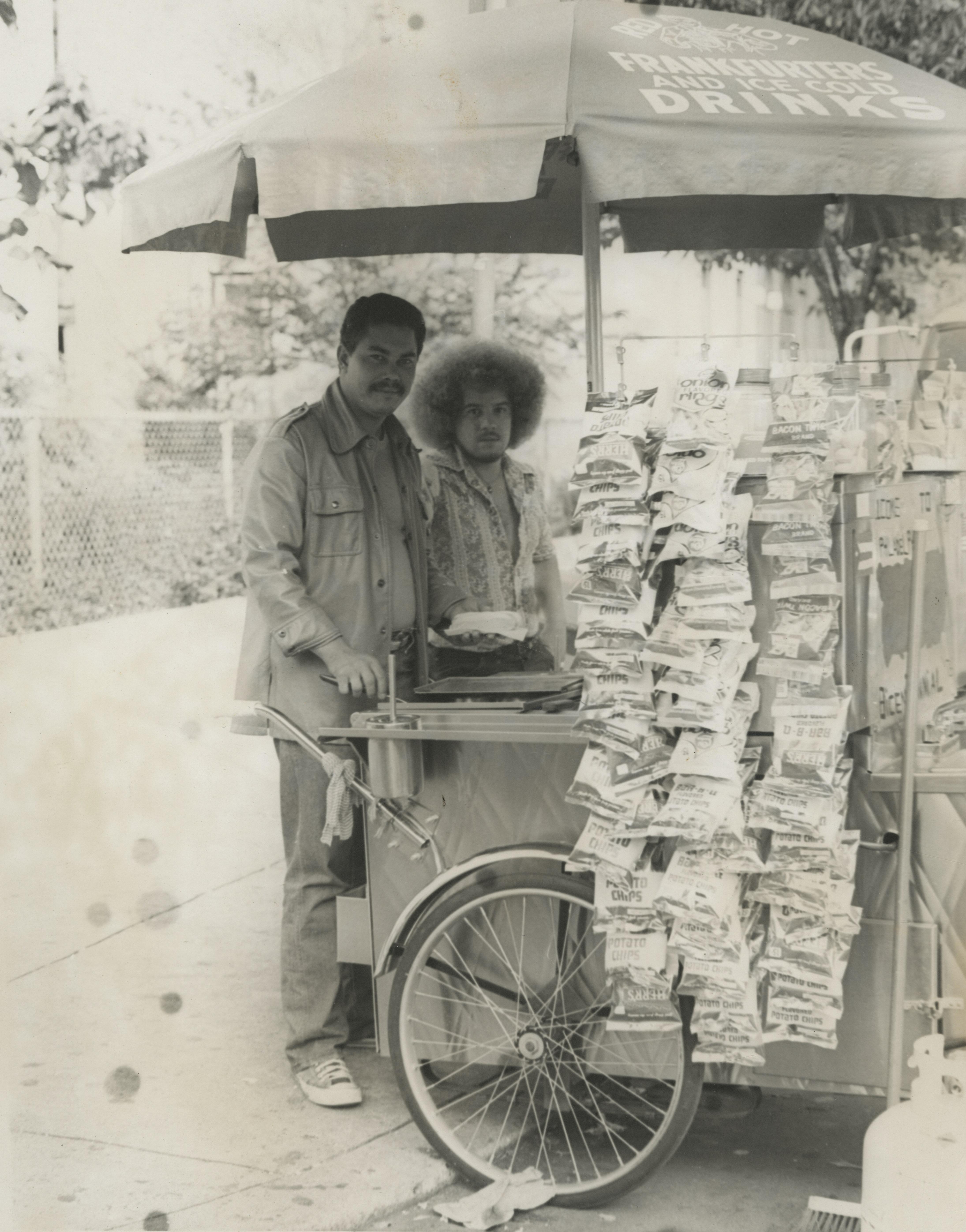 Dos hombres se unen junto a un carro de vendedores